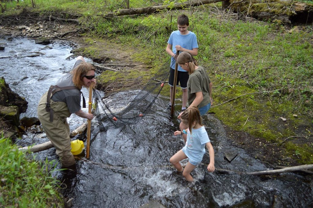 Jenny Kruckenberg teaches willing children the darter shuffle in the bone-chilling creek water, hoping to catch some brilliantly colored natives!